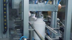 Uma máquina pressiona as garrafas brancas quando se moverem em uma linha, produção moderna filme