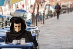 Uma máscara falsificada tem o pequeno almoço em Veneza Imagem de Stock