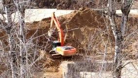 Uma máquina escavadora em um canteiro de obras escava um furo video estoque