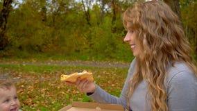 Uma mãe alimenta a sua pizza um rapaz pequeno Piquenique da família no parque do outono filme