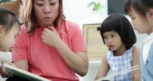Uma mãe caucasiano e suas crianças olharem desenhos animados engraçados em desenhos animados registrar quando junto em casa video estoque