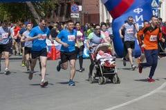 Uma mãe com um bebê em um transporte de bebê corre o meio Kremlin de Ryazan da maratona dedicado ao ano de ecologia em Rússia Imagem de Stock