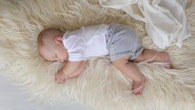 Uma mãe de inquietação cobre sua criança de sono recém-nascida com uma cobertura macia filme
