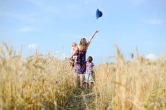 Uma mãe e duas crianças que andam afastado através de um campo Fotografia de Stock Royalty Free