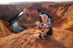 Uma mãe e seu bebê estão sentando-se na borda Fotografia de Stock Royalty Free