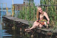 Uma mãe e um filho novos estão descansando na ponte pelo rio Conceito do estilo de vida imagem de stock royalty free