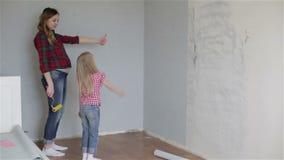 Uma mãe e uma filha pequena satisfeitas com seu wallpapering vídeos de arquivo
