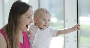 Uma mãe feliz bonita com seu menino do menino que está na frente da janela grande e que olha para fora vídeos de arquivo