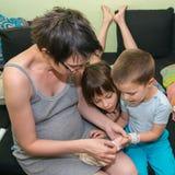 Uma mãe grávida envolve a mão do seu filho foto de stock