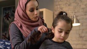 Uma mãe indiana nova que veste um hijab fizer um penteado a suas filha e negociações pequenas, quando criança que lê um livro vídeos de arquivo