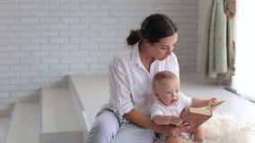Uma mãe lê um livro a sua criança recém-nascida, eles senta-se no assoalho na cobertura macia video estoque