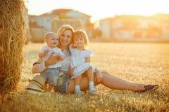 Uma mãe nova com duas crianças - um bebê pequeno e uma menina fotos de stock royalty free