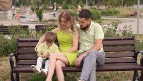 Uma mãe nova com seu marido e um filho novo estão sentando-se no parque no banco filme