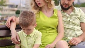 Uma mãe nova com seu marido e um filho novo estão sentando-se no parque no banco vídeos de arquivo