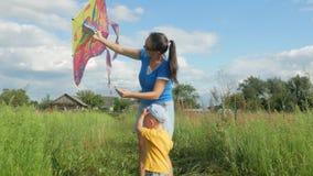 Uma mãe nova com um bebê lança um papagaio do ar em um campo verde no verão A mãe não faz bem Filho muito feliz vídeos de arquivo