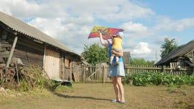 Uma mãe nova com um bebê lança um papagaio do ar em um campo verde no verão A mãe não faz bem Filho muito feliz video estoque