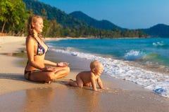 Uma mãe nova com uma criança que tem o divertimento em uma praia tropical nações Imagens de Stock Royalty Free