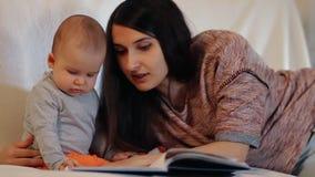 Uma mãe nova e uma criança pequena que leem um livro Tiro do movimento lento filme