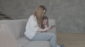 Uma mãe nova e uma filha pequena com o cabelo longo que senta-se junto no sofá na sala de visitas usando a tabuleta E video estoque