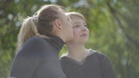 Uma mãe nova e seu filho adolescente que descansam no parque junto A mulher que beija sua criança no mordente, beija-a vídeos de arquivo