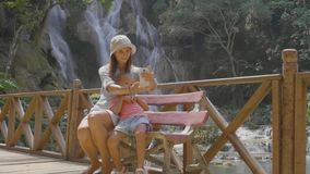 Uma mãe nova e sua filha bonito que descansam contra a cascata de uma cachoeira filme