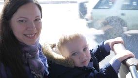 Uma mãe nova e um menino estão montando em um ônibus Sorriso e olhar na câmera filme