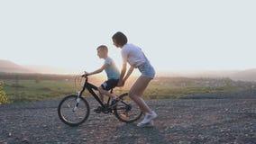 Uma mãe nova ensina seu filho conduzir em uma bicicleta no verão no por do sol ou no nascer do sol Uma mulher guarda uma biciclet filme