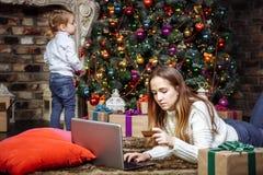 Uma mãe nova está fazendo a compra em linha com portátil e cartão de crédito quando sua filha decorar a árvore de Natal fotografia de stock