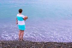 Uma mãe nova está na praia com seu bebê de sono Foto de Stock