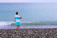 Uma mãe nova está na praia com seu bebê de sono Imagens de Stock Royalty Free