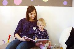 Uma mãe nova lê um livro do ` s das crianças para uma criança Imagens de Stock