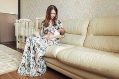 Uma mãe nova que balança uma criança em seus braços imagem de stock