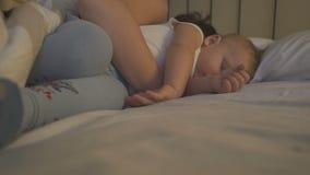 Uma mãe nova que dorme com seu filho no punho vídeos de arquivo