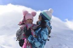 Uma mãe nova viaja nas montanhas com sua pouca filha em um inverno ensolarado fotografia de stock