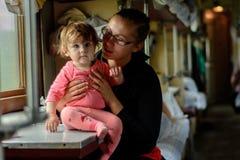 Uma mãe nova viaja nos vidros junto com uma filha maravilhosamente bonita fotografia de stock