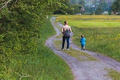 Uma mãe que anda com seu filho imagens de stock
