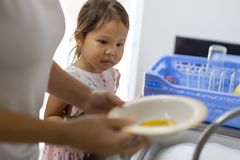 Uma mãe que ensina a sua criança como lavar em casa pratos fotos de stock