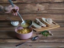 Uma mão com uma concha derrama a sopa de ervilha Alimento rústico fotografia de stock