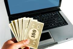 Uma mão com dinheiro na frente de um computador Foto de Stock