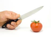 Uma mão com faca e tomate Fotografia de Stock Royalty Free