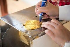 Uma mão com a pena azul para escrever o nome na folha de ouro fotos de stock royalty free