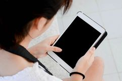 Uma mão da menina guarda a tabuleta digital branca no parque foto de stock