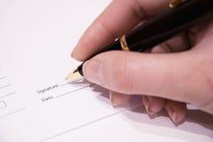 Uma mão da mulher assina uma pena de papel do negócio Foto de Stock