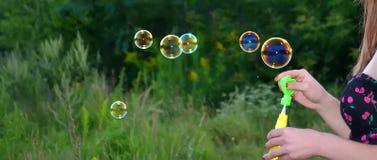 Uma mão de bolhas de sabões da menina imagens de stock
