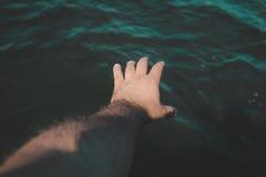 Uma mão de uma tentativa do homem para travar algo na água Imagem de Stock