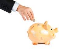 Uma mão do homem de negócios que introduzem uma moeda em um mealheiro isolado, o conceito para o negócio e salvar o dinheiro Foto de Stock Royalty Free