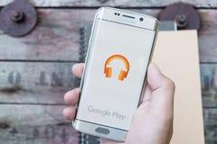 Uma mão do homem que guarda a captura de tela da música do jogo de Google Foto de Stock