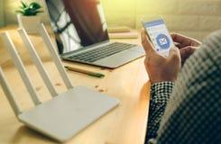 Uma mão do homem usando o telefone celular com aplicação do email fotografia de stock