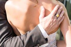Uma mão do noivo com anel com a pedra amarela no bride's empurra fotografia de stock royalty free
