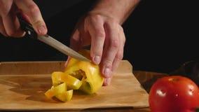 Uma mão do ` s do cozinheiro corta uma pimenta de sino por uma faca em uma placa de corte filme